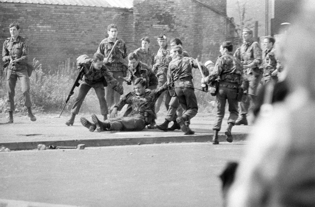 An injured soldier is dragged away by his comrades during a riot in the Falls Road, Belfast, on the first day of Queen Elizabeth II's Silver Jubilee visit to Northern Ireland. Ref #: PA.11734482  Date: 10/08/1977
