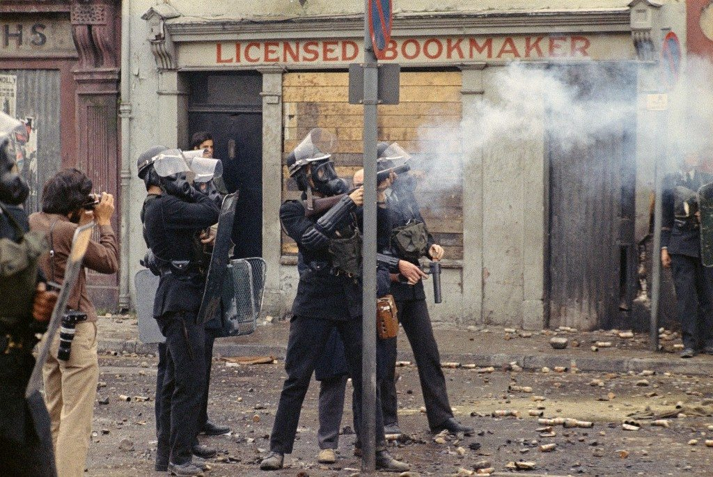 Riot police wearing helmets and gas masks during disturbances with Catholic rioters along a street in the Bogside area of Londonderry, Northern Ireland on Aug. 13, 1969. (AP Photo/Peter Kemp) Ref #: PA.11810340