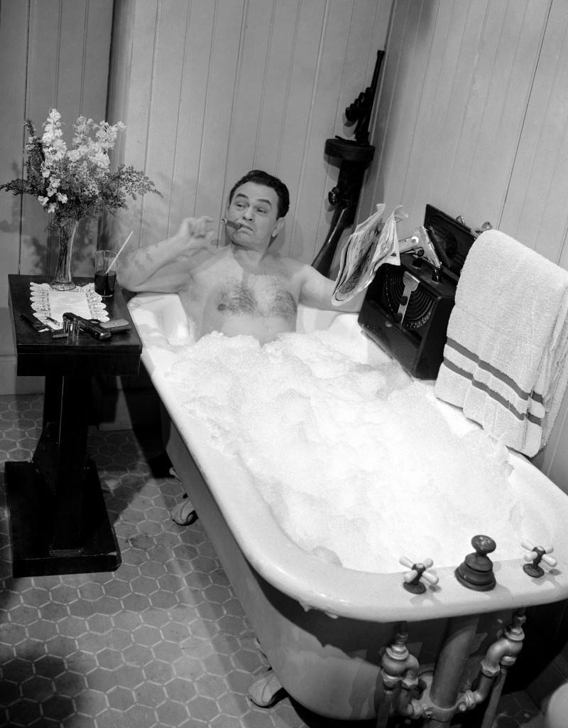 """Actor Edward G. Robinson portrayer of """"tough guy"""" parts in the movies, does his best to keep a stern face as he underwent a bubble bath in a movie scene in Hollywood on March 17, 1948. He has his inevitable cigar. (AP Photo)"""