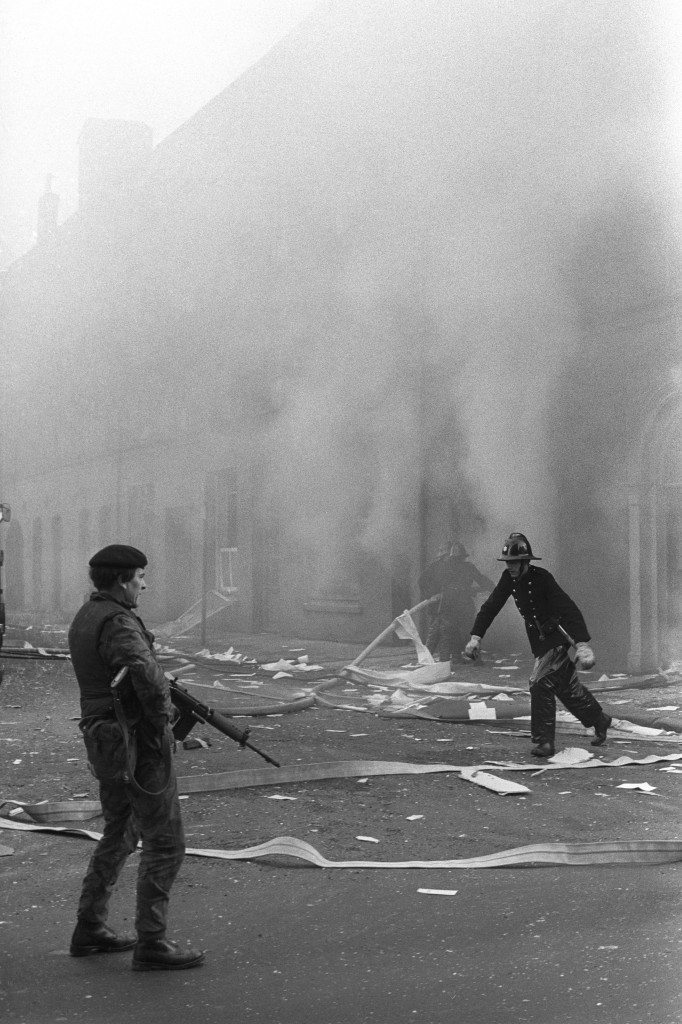 A British soldier guards firemen fighting a blaze after a bomb blast at a miller's beside the River Foyle in Londonderry, when bombers opened a new offensive in the city in response to the shooting deaths of 13 civilians at the weekend by British soldiers. Ref #: PA.12441676 Date: 03/02/1972