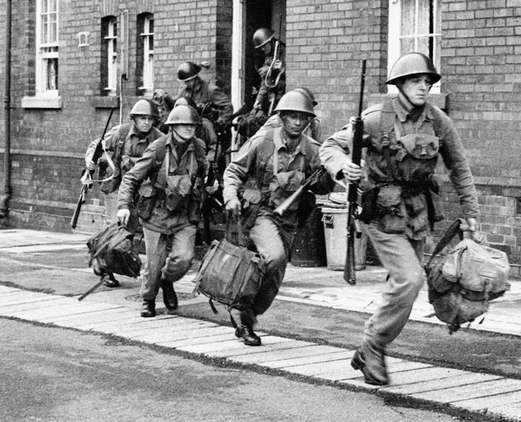 Troops sprint from their barracks in Holywood, near Belfast to board a truck to take up guard duty.