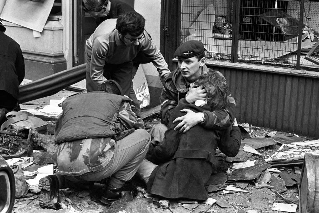 A British paratrooper takes a young girl in his arms to comfort her after she had been hurt in the bomb blast in Donegal Street, Belfast. Ref #: PA.1666851 Date: 20/03/1972