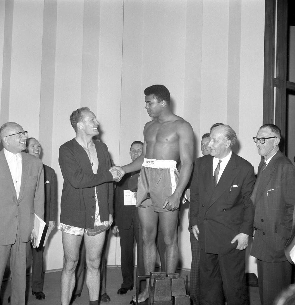 American heavyweight Cassius Clay shakes hands with British heavyweight champion Henry Cooper during the weigh-in at London Palladium. Clay continued his confident boastings that he will beat British heavyweight champion Henry Cooper in five rounds in their fight at Wembley Stadium tonight. Archive-pa103725-1a Ref #: PA.16676129 Date: 18/06/1963