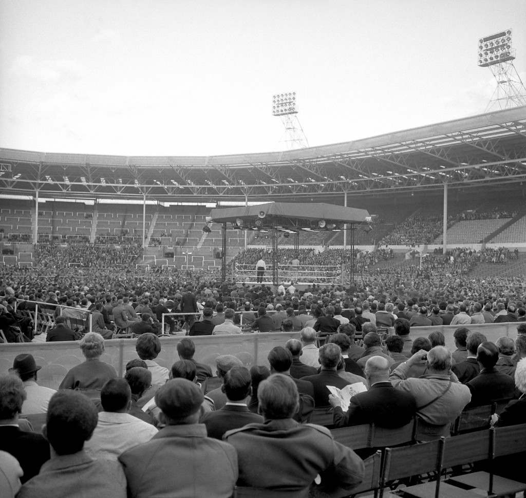 The crowd enjoy London's first open-air boxing match for many years during one of the preliminary matches held at Wembley Stadium before the heavyweight fight between American heavyweight Cassius Clay and British Champion Henry Cooper. Archive-pa103725-10 Ref #: PA.16676137 Date: 18/06/1963