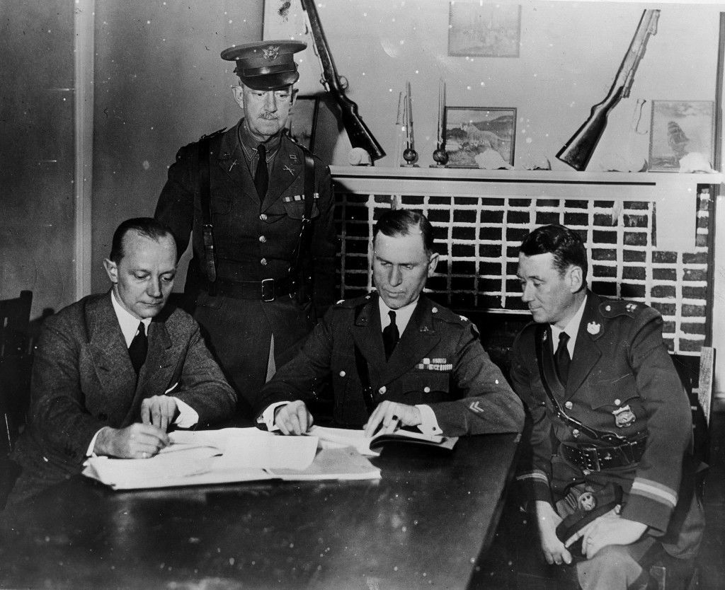 Maryland State Troopers in charge of the campaign to apprehend a group of lynchers work out a plan of attack in Salisbury, Md., Nov. 28, 1933. From left: Attorney General W. Preston Lane Jr.; Col. Washington Bowie; Brigadier General Milton A. Reckord, state adjutant general; and Capt. Edward Mck. Johnson of the Maryland State Police. (AP Photo) Ref #: PA.20299308  Date: 28/11/1933