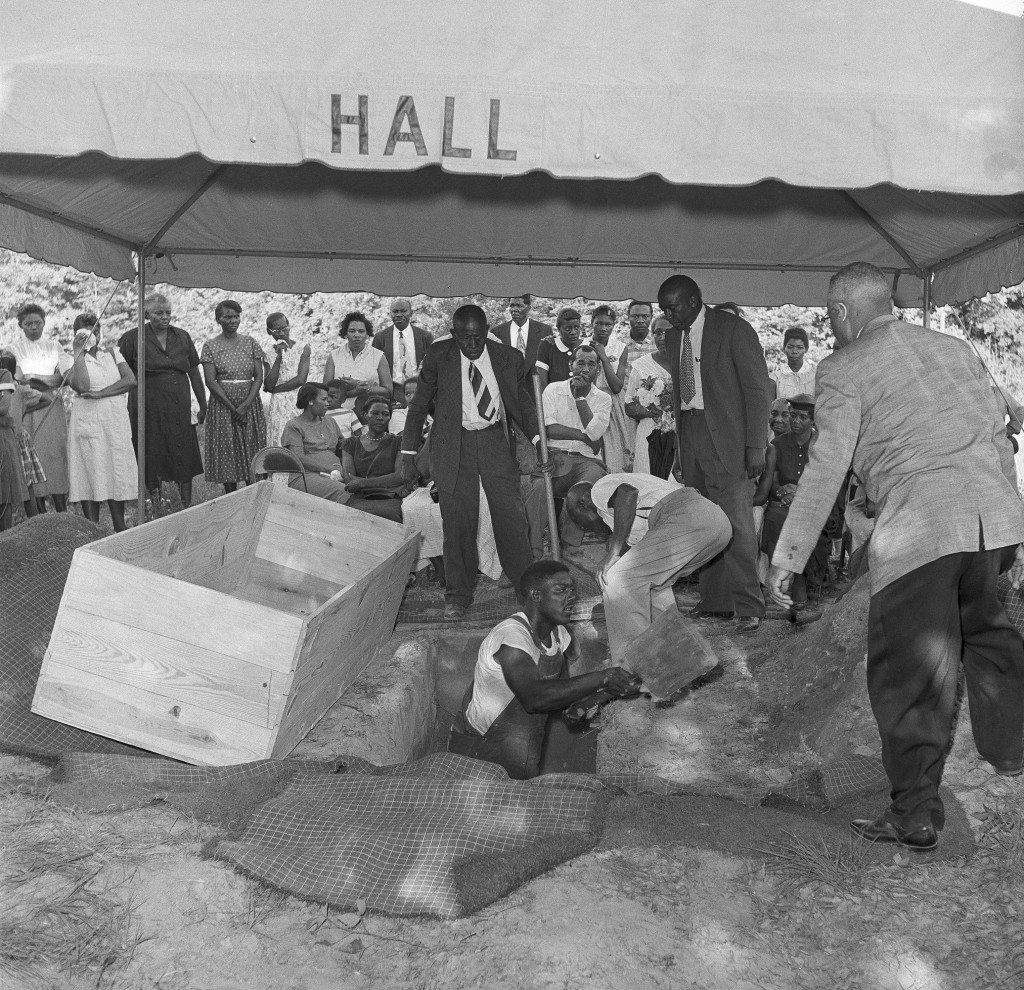 A gravedigger delays the burial service for Mack Charles Parker, 23-year-old African-American man accused of rape, to widen the grave for the pine box, left, in Lumberton, Miss., May 5, 1959. Grief is written on the faces of relatives and friends of Parker, who was the victim of a lynch mob. Parker's body was retrieved from the Pearl River the previous day. About 100 African-Americans and 20 newsmen witnessed the burial. (AP photo/Richard Tolbert) 1959.