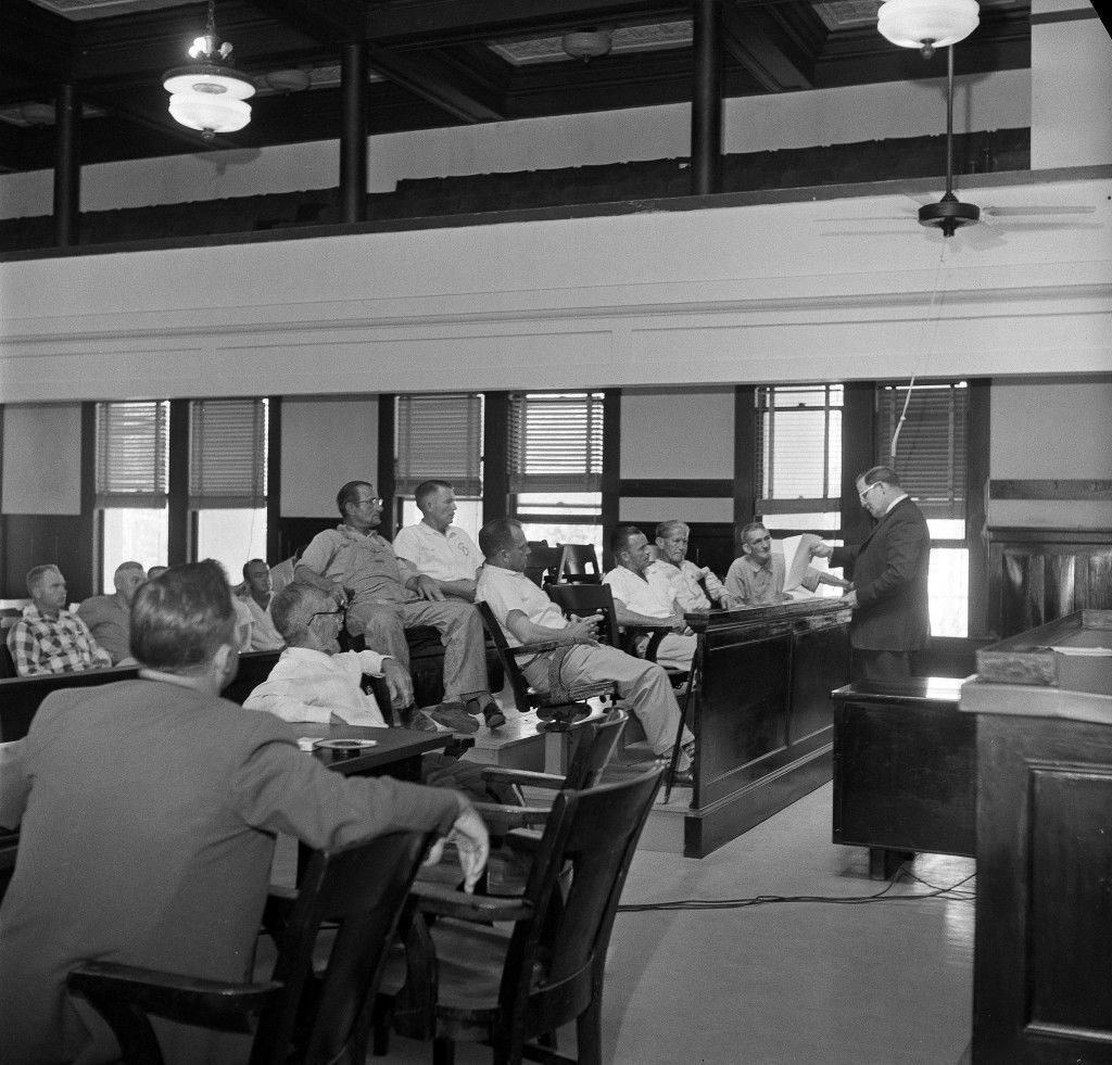 "A six-member jury at a coroner's inquest into the lynch mob death of Mack Charles Parker, a 23-year-old African-American accused of rape, hears County Attorney William Steward, right, read the autopsy report, in Poplarville, Miss., May 5, 1959. Justice of the Peace Walter Davis, who conducted the hearing, sits left, foreground. Parker's body was found in the Pearl River yesterday. The jury ruled he died from ""two high speed projectiles,"" probably bullet wounds, inflicted by an unknown person or persons. District Attorney Vernon Broom can be seen on the extreme left, with his back to the camera. (AP Photo/Richard Tolbert)"