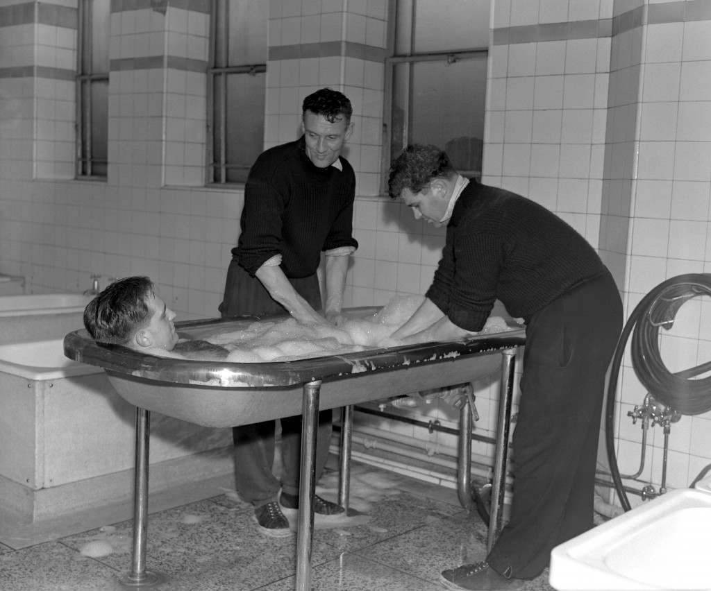 (L-R) Arsenal's Doug Lishman enjoys a soap foam bath massage, performed by coach Alf Fields and Les Compton