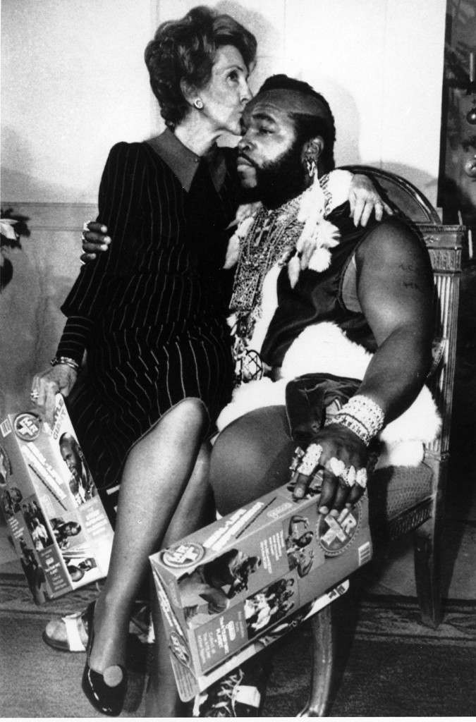 First lady Nancy Reagan sits on the knee of television personality Mr. T, dressed as Santa Claus, as he joined her for a preview of the White House Christmas decor in Washington, D.C. Picture date: Dec. 12, 1983.(AP Photo/Ira Schwarz) Ref #: PA.2372892
