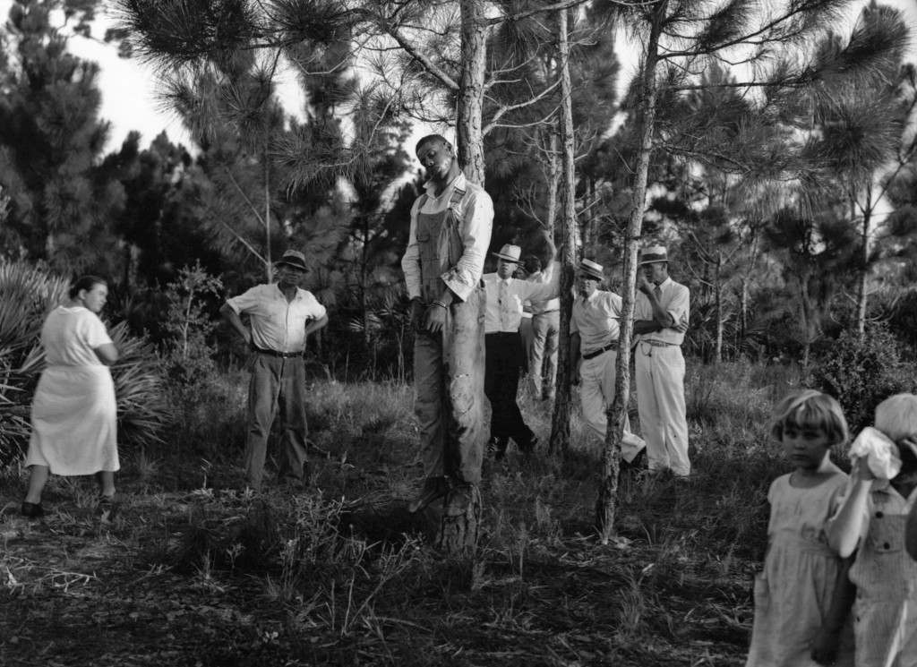 The body of 32-year-old Rubin Stacy hangs from a tree in Fort Lauderdale, Fla., as neighbors visit the site. Stacy was lynched by a mob of masked men who seized him from the custody of sheriff's deputies for allegedly attacking a white woman. Ref #: PA.2480694  Date: 19/07/1935