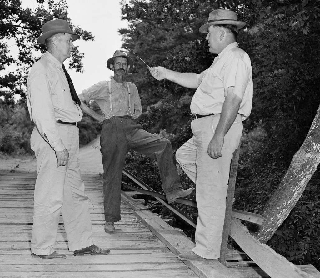 Loy Harrison, right, in this photo taken July 26, 1946, shows Oconeee County Sheriff J.M. Bond, left, and Coroner W.T. Brown of Walton County, center, the spot where four blacks had been abducted from his car. On July 25, 1946 George Dorsey, Mae Murray Dorsey, Roger Malcom and Dorothy Malcom were lynched by a mob on the old bridge that spanned the Apalachee River some 60 miles from Atlanta.