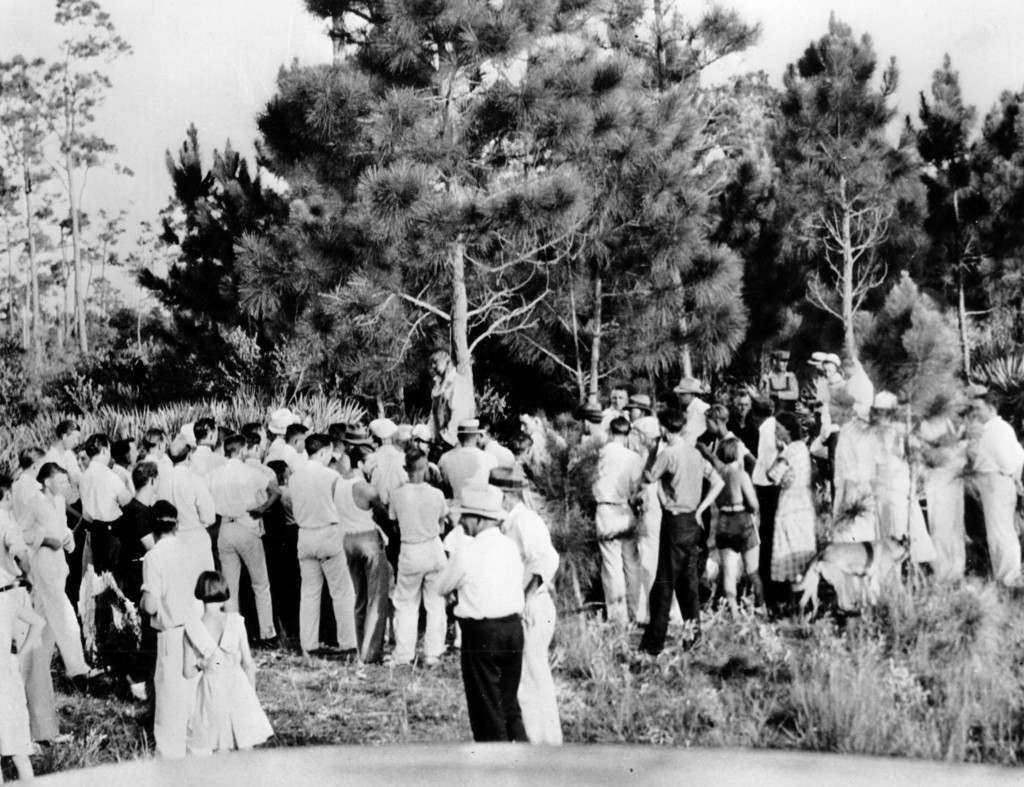 A crowd gathers to view the body of 32-year-old Rubin Stacy as he hangs from a tree in Fort Lauderdale, Fl., on July 19, 1935. Stacy was lynched by a mob of masked men who seized him from the custody of sheriff's deputies for allegedly attacking a white woman. Ref #: PA.2499602