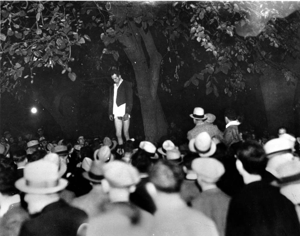 A crowd looks on as Thomas Thurmond hangs from a tree limb after he was beaten by a lynch mob in San Jose, Ca. Thurmond, along with Jack Holmes, confessed the kidnap-slaying of 22-year-old Brooke Hart of San Francisco. Ref #: PA.2499605  Date: 26/11/1933