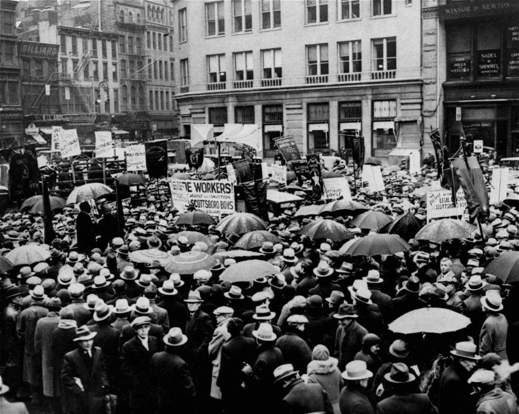 "More than 1,200 braved disagreeable weather to attend a rally in Union Square, New York City, December 9, 1933, on behalf of the nine Scottsboro boys. The meeting was arranged by the International Labor Defense and was backed by the Communist Party. The marchers carried banners and a sign with the image of a lynching, and the legend ""Alabama - The land of the tree and the home of the grave."""