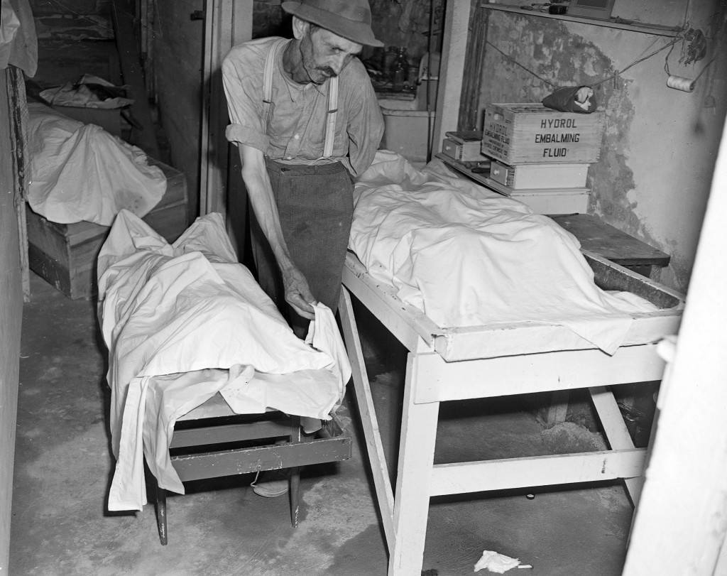Coroner W.T Brown places a sheet over the body of one of four African American mob victims in a funeral home at Monroe, Ga., in a July 26, 1946 file photo. Newly released files from the lynching of two black couples more than 60 years ago contain a disturbing revelation: The FBI investigated suspicions that a three-term governor of Georgia sanctioned the murders to sway rural white voters during a tough election campaign. (AP Photo, File)