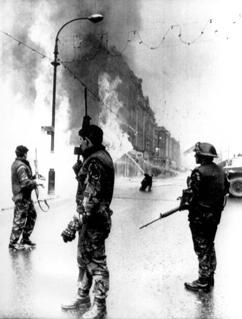 British soldiers stand guard as a department store goes up in flames in the center of Londonderry, Northern Ireland, on Jan. 4, 1972. In center background, a fireman directs water into the blaze. The fire followed explosion of a bomb planted in the building by Irish Republican Army (IRA) terrorists. (AP Photo) Ref #: PA.4885228