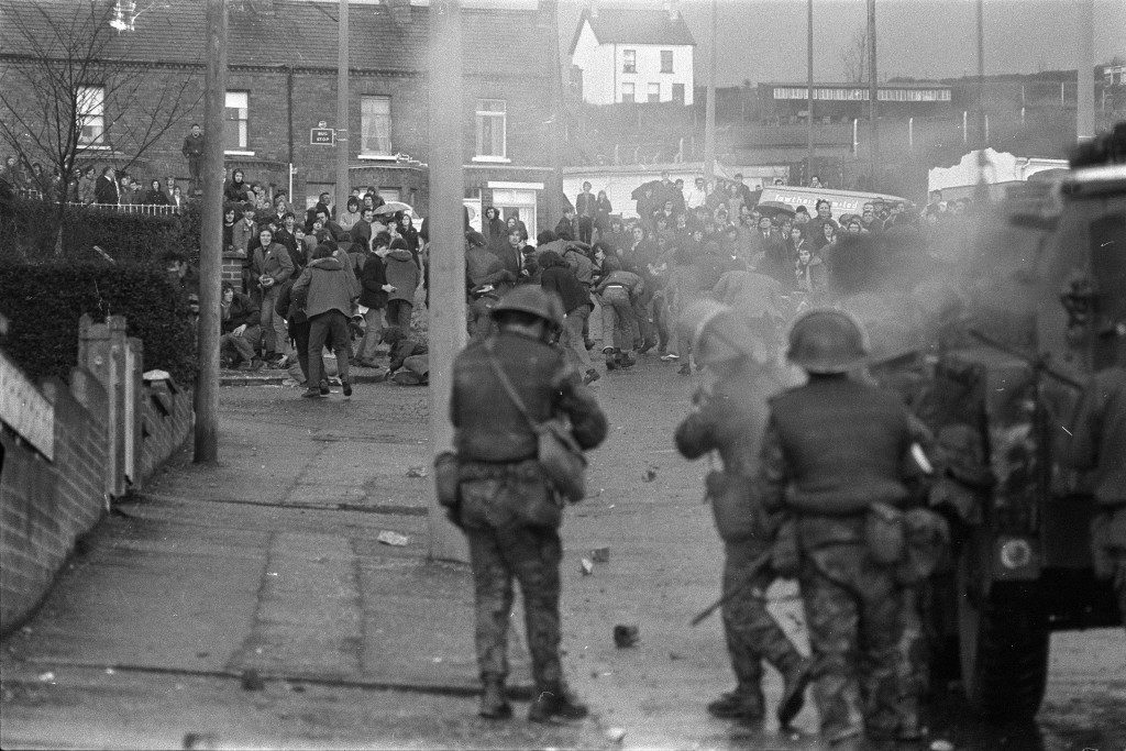 British troops fire rubber bullets at stone-throwing Protestant rioters who had set fire to the mobile classrooms of Our Lady of Mercy Secondary School in the Ballysillian area of west Belfast, Northern Ireland, March 28, 1972. (AP Photo/Michel Lipchitz) Ref #: PA.4885238