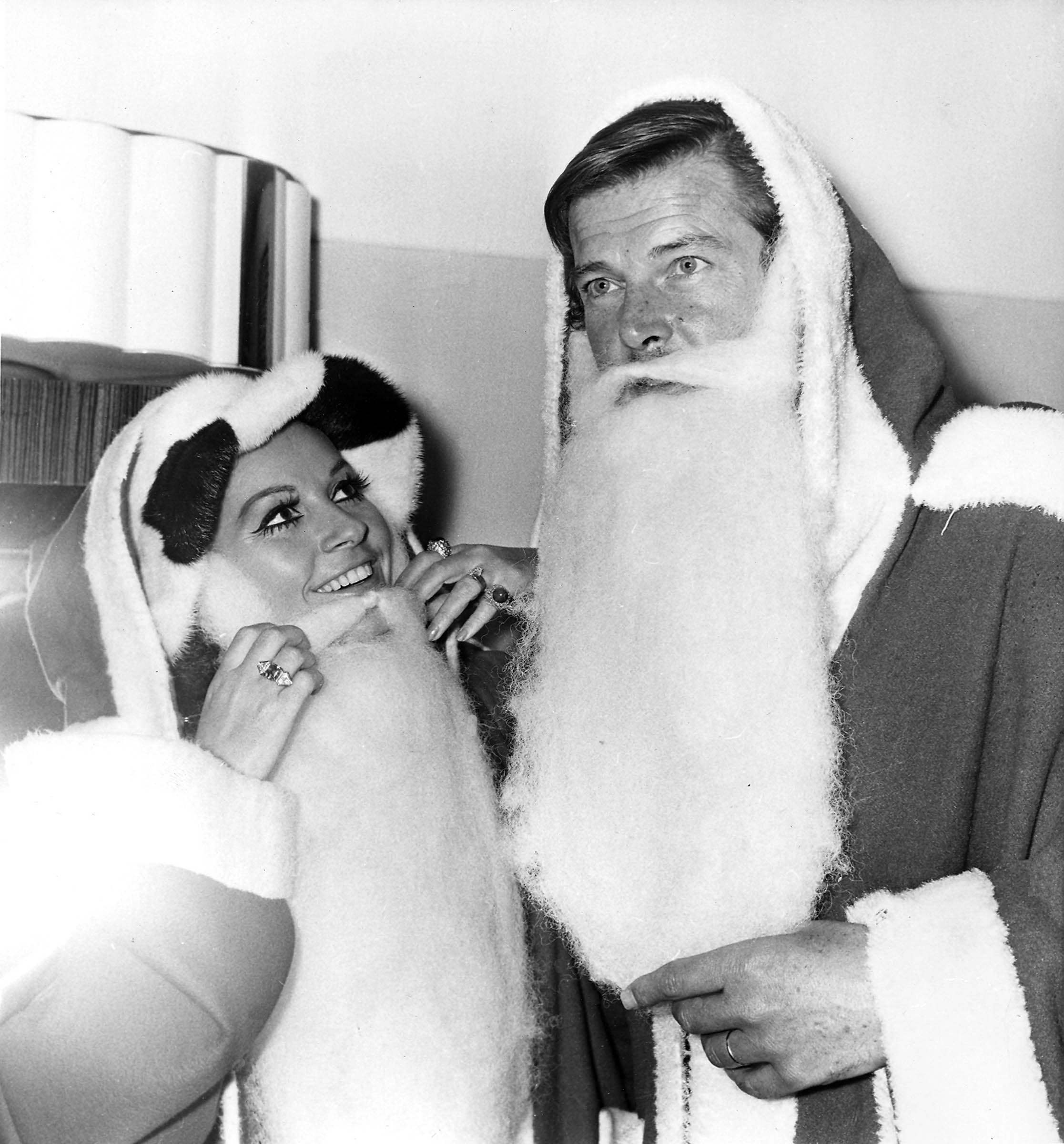 "Actors Luisa Mattioli and her husband Roger Moore don ""Father Christmas"" costumes at the Variety Club of Great Britain's Christmas luncheon at the Savoy Hotel in London, Dec. 9, 1969. They are collecting gifts for sick and deprived children. (AP Photo/Bob Dear) Ref #: PA.4942328 Date: 09/12/1969"