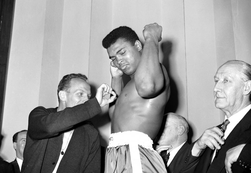 (L-R) Henry Cooper plucks a hair from Cassius Clay's chest as Clay admires his own muscles Ref #: PA.535569