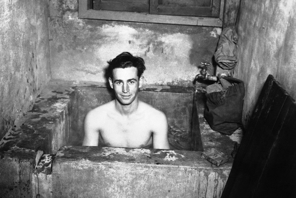 Pfc. Merrill H. Small, of New Paltz, New York, enjoys a bath?native style?during break in action against Chinese Communist forces in Korea on Jan. 23, 1951. He is a member of a Heavy Mortar Co., 5th Cavalry regiment, 1st Cavalry Division. (A Photo)