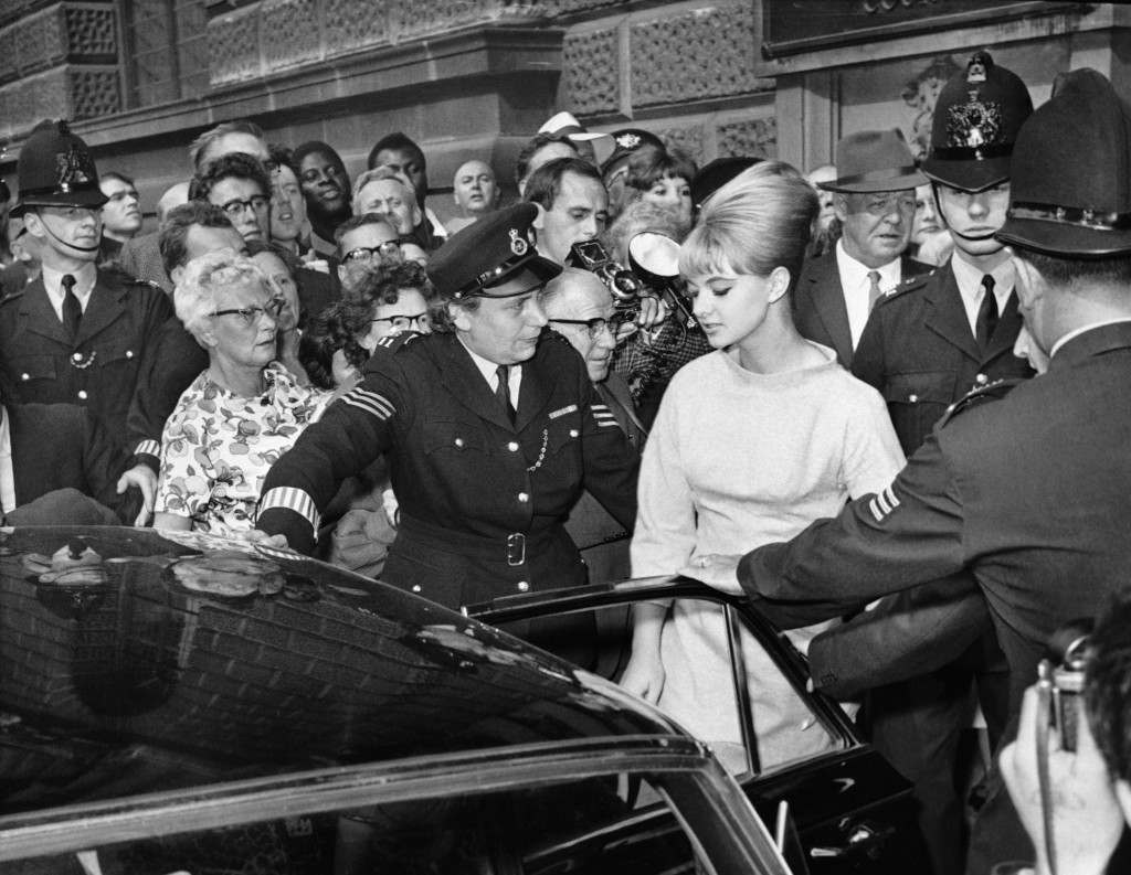 Police escort Mandy Rice-Davies a witness in the trial of vice charges of Osteopath Dr. Stephen Ward, to a car in London on July 22, 1963, after the first day of ward?s trial. The trial, which is being held at the Old Bailey Central Criminal Court, would last a fortnight. (AP Photo) Ref #: PA.8600593