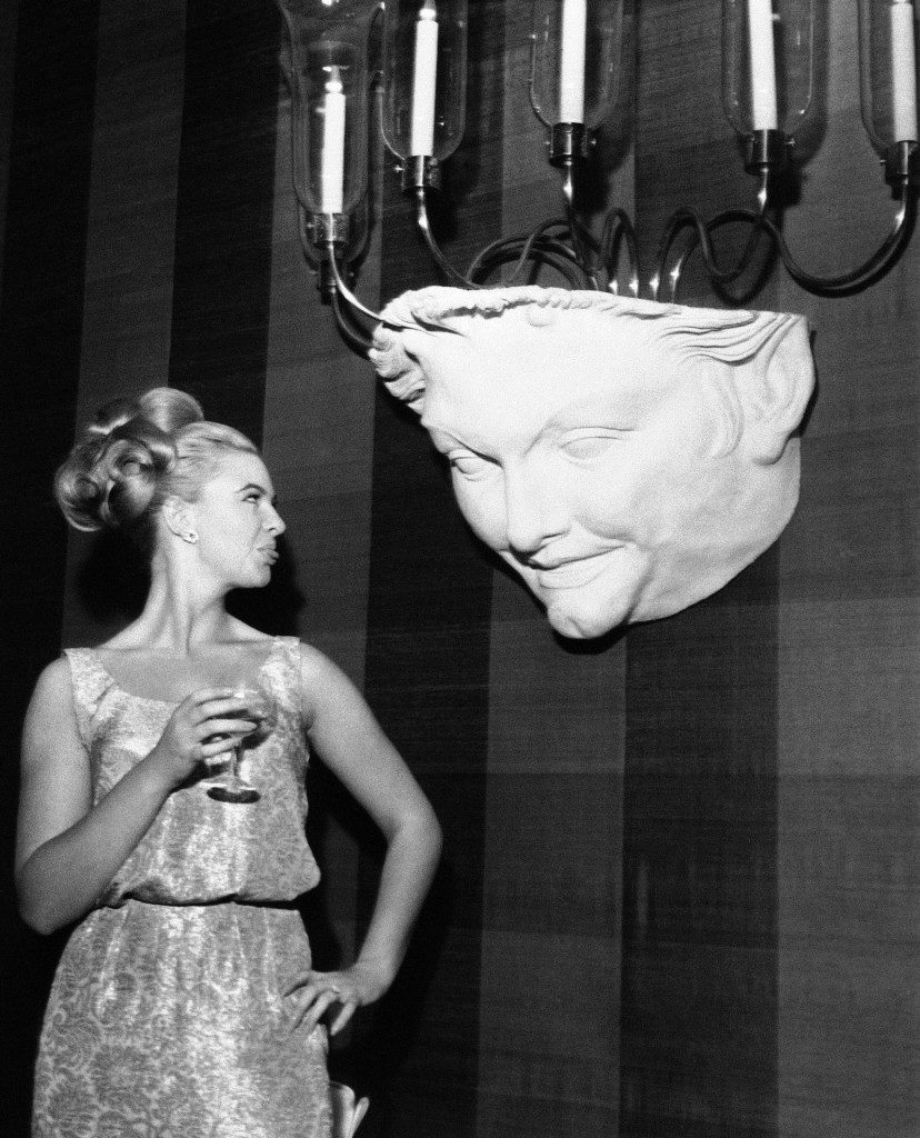 Mandy Rice-Davies, 18-year-old prosecution witness in the vice trial of Dr. Stephen Ward in London, sticks out her tongue in apparent appraisal of decorative chandelier at an opening night party for film ?Cleopatra,? on July 31, 1963, Mandy, her hair piled high gave cameramen the same treatment. Three guests at the part walked out when they found themselves seated at Mandy?s table. (AP Photo) Ref #: PA.8600606  Date: 31/07/1963