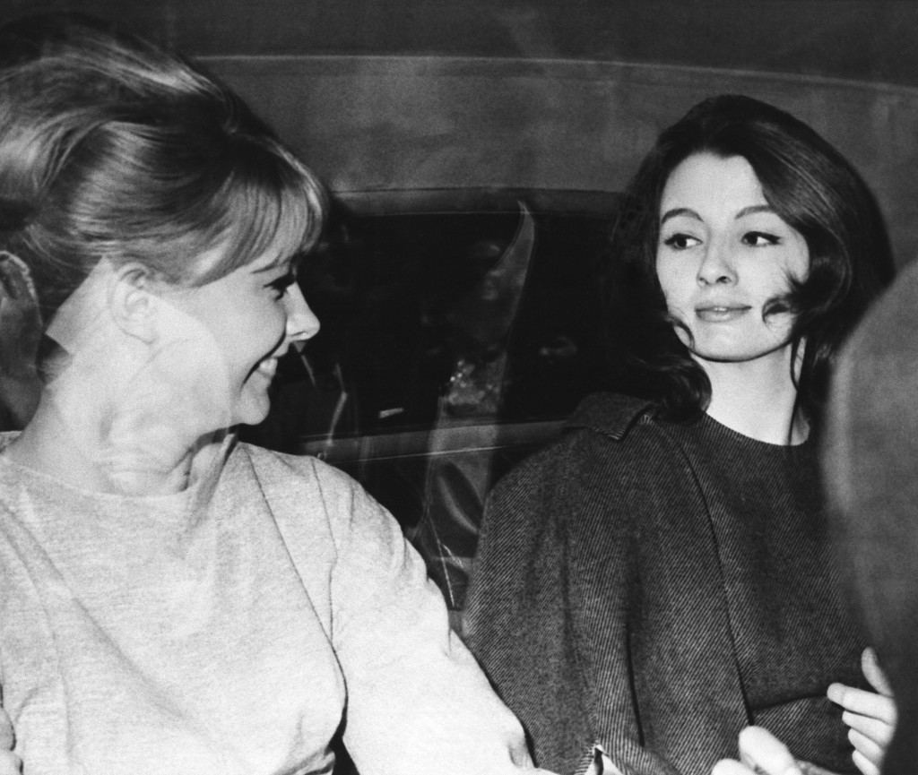Christine Keeler, right, and Mandy Rice-Davies sit in cab leaving Old Bailey Court in London on July 22, 1963. Part of crowd gathered around cab is reflected in windows. Girls are among prosecution witnesses in the trial of Dr. Stephen Ward. Jury trial opened on July 22 for the doctor who is charged on five counts of living off the earnings of prostitutes. (AP Photo) Ref #: PA.8616915