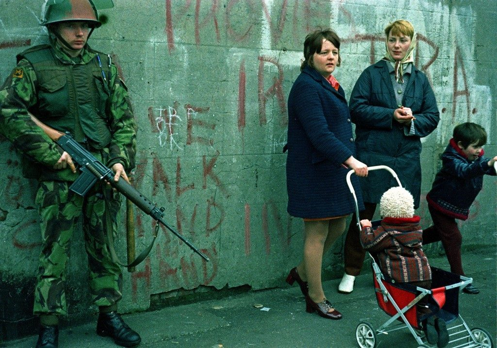 Women and children stand near an armed British military soldier patrols a street in Belfast, Northern Ireland, Feb. 1972. British paratroopers shot 13 demonstrators during a civil rights march on Jan. 30, known as Bloody Sunday. (AP Photo/Michel Laurent) Ref #: PA.8647620