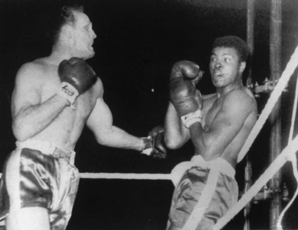 Cassius Clay, bewildered by Henry Cooper's unexpected and ferocious opening attack, is shown pinned on the ropes in the first round of their heavyweight match at Wembley Stadium, London, June 18, 1963. (AP Photo)