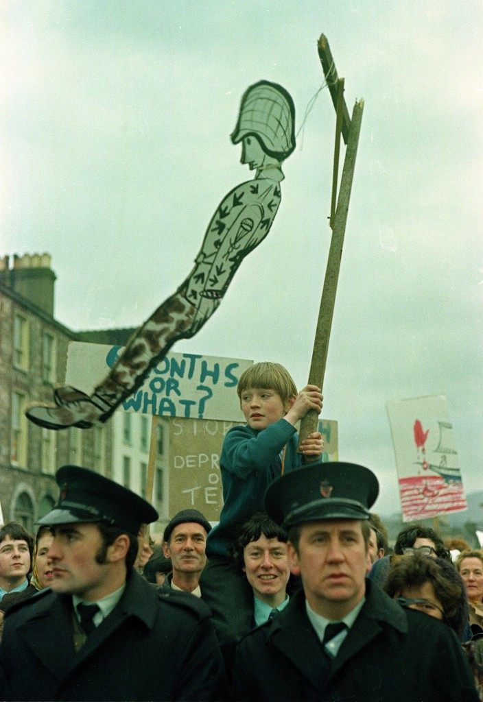 A young child, resting on a man's shoulders, holds a hanging effigy of a British soldier during a march in Belfast, capital of Northern Ireland, Feb. 1972. The rally follows the deadly shooting of 13 demonstrators by British paratroopers during the civil rights march on Jan. 30, known as Bloody Sunday. (AP Photo/Michel Laurent) Ref #: PA.8693089