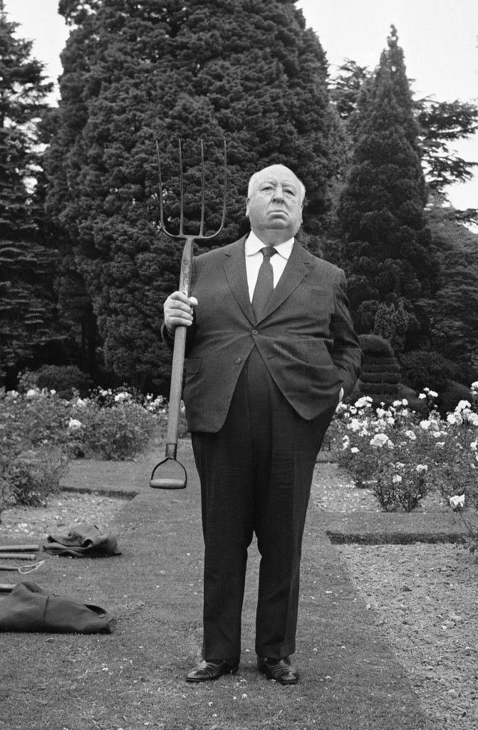 British film producer and director Alfred Hitchcock, who will be 72 next month, stands with a pitchfork on the lawns of Pinewood Studios, at Iver, Buckinghamshire, United Kingdom on July 22, 1971.