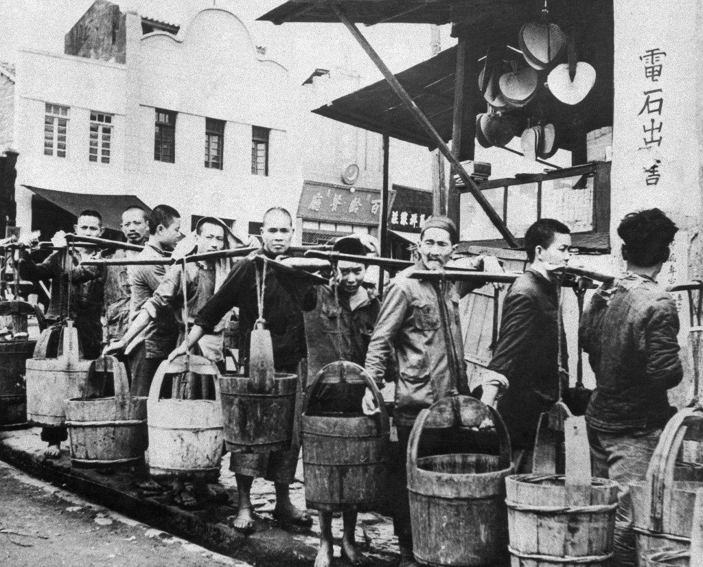 ChungkingÂs water is a commodity on sale at certain distribution centers. Here, a line of coolies wait to fill their wooden tubs, carried in old-time milkmaid fashion, slung from a shoulder strut in China, July 29, 1944. (AP Photo)
