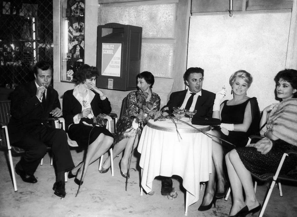 "Seated for a bit of rest between scenes are from left to right: Italian actor Marcello Mastroianni holding a cigarette; French actress Anouk Aimee; Austrian-born actress Luise Rainer; Italian star director Federico Fellini; Swedish-born actress Anita Ekberg holding a cigarette and French actress Yvonne Fourneaux. Picture was made in Rome, Italy on June 6, 1959 in a shooting break of the movie ""La Dolce Vita"" (The Sweet Life), directed by Fellini and starring Marcello Mastroianni. The others in the picture have parts in the film, too – the most important one, besides Mastroianni's, is Miss Ekberg's. They relax on the set built up of a Via Veneto section for a gay outdoor-party scene. The movie deals with the activities of a newsman who specializes in scandal stories. (AP Photo/Mario Torrisi)"