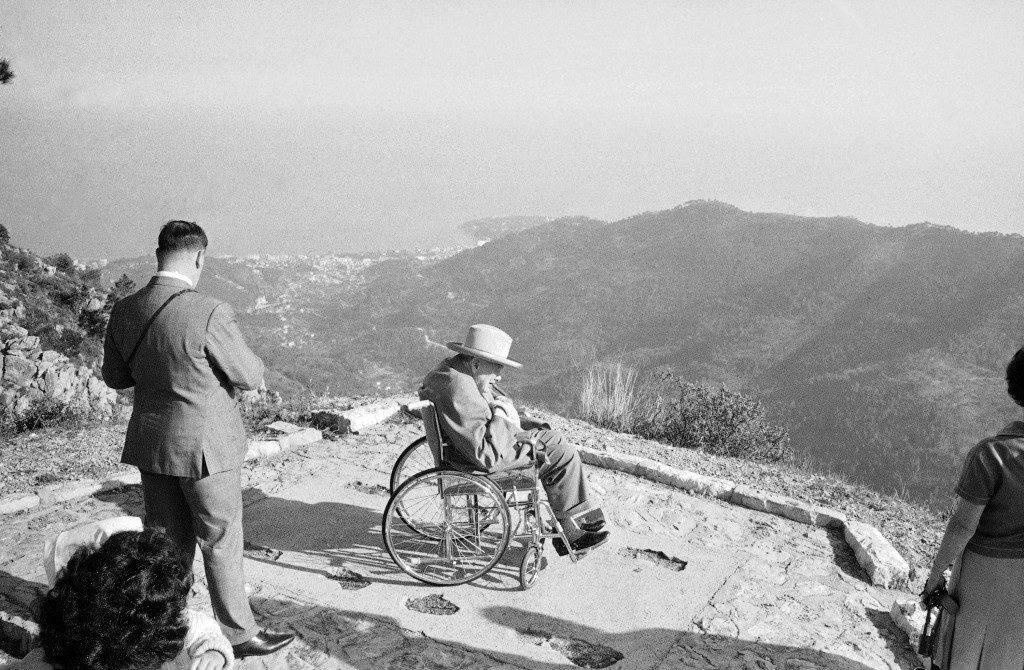 Puffing on his inseparable cigar, Sir Winston Churchill views the Riviera Town of Menton from his wheelchair on the Col De La Madone during a visit to St. Agnes in Monaco on April 22, 1963. Sir Winston is spending a sunshine holiday at the Hotel De Paris in Monte Carlo. (AP Photo/N)