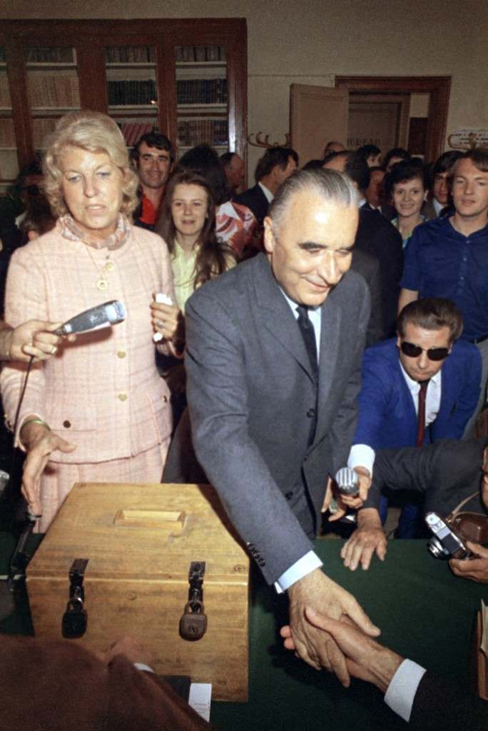 "Former French premier Georges Pompidou and his wife Claude Pompidou on June 15, 1969 in France are seen as they cast their votes in the French presidential election run-off at Orvilliers, outside Paris, then walk outside past group waving French Tricolor flag and a sign reading ""the youth of Richebourg want Pompidou."" (AP Photo/Michel Lipchitz)"