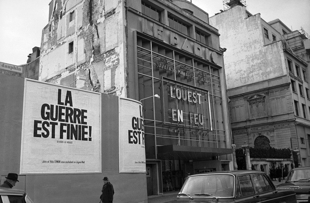 A poster which reads La Guerre est Fine which translates to The War is Over is displayed on the Champs Elysees in Paris, France on December 12, 1969. It is part of a series of posters by John Lennon and his wife Yoko Ono, both unseen, which are being displayed in eleven cities around the world. They also wish people a Merry Christmas. (AP Photo/Cardenas)