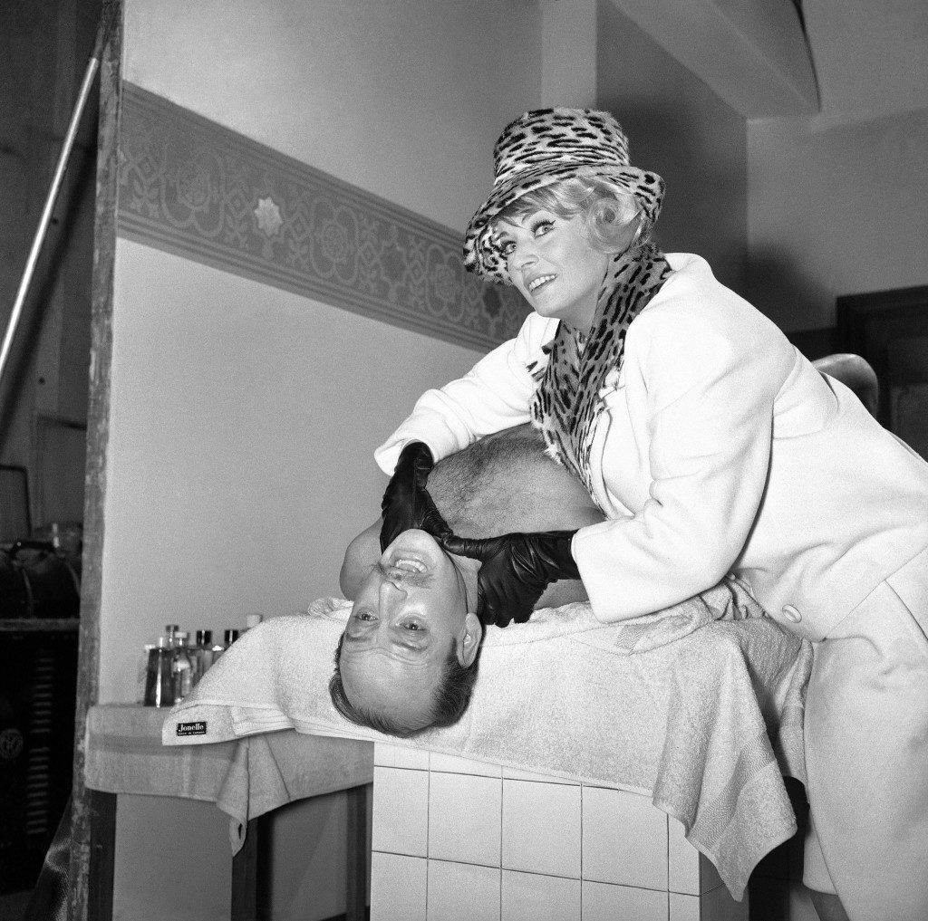 "Tony Randell, star of the new Metro-Goldwyn-Mayer film ""The A.B.C. Murders"", based on the Agatha Christie' novel of the same name, gets some rough treatment from the female lead, Sweden's Anita Ekberg, during the first days filming at the M.G.M. studious at Borehamwood, Hertfordshire, England, United Kingdom, on Nov. 25, 1964. In the film Randell plays the part of the famous Belgian detective Hercule Poirot and Anita as a clamorous blonde who helps him solve a series of bizarre murders in London. (AP Photo/Victor Boyton) Ref #: PA.11721250"
