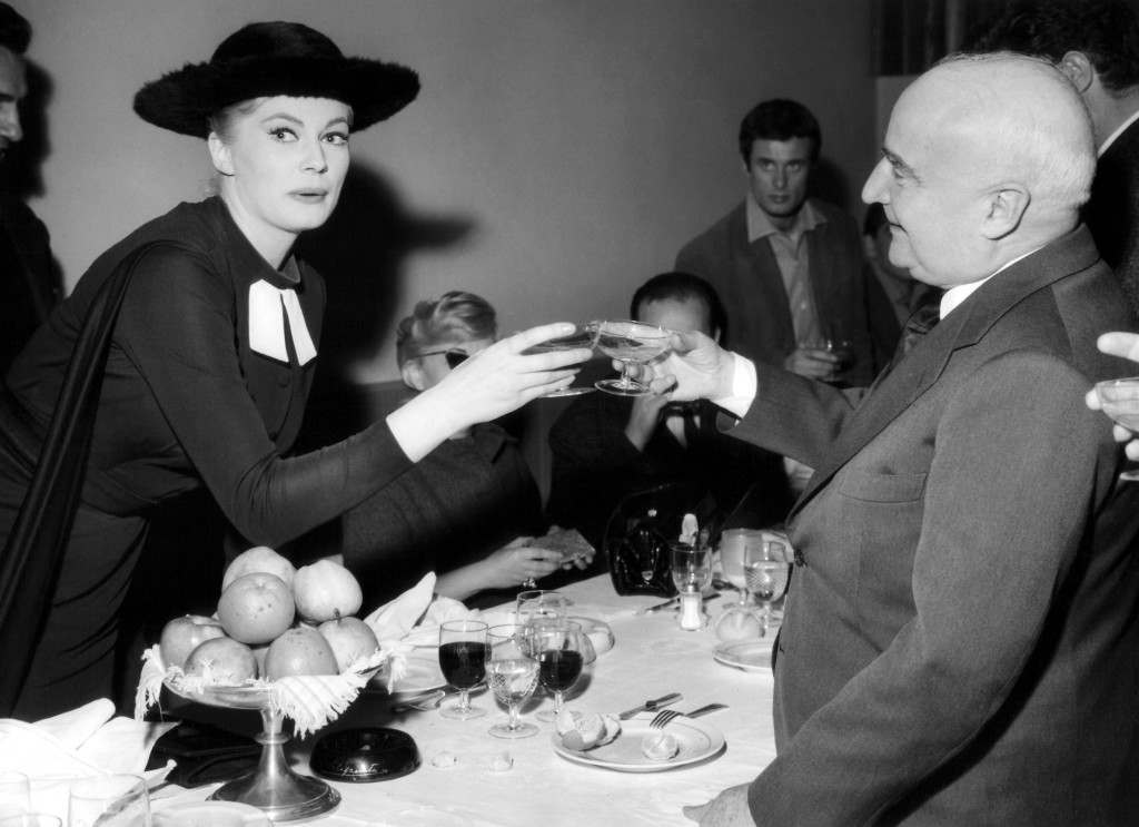 "Swedish movie actress Anita Ekberg toasts with producer Angelo Rizzoli, producer of the film ""The Sweet Life"" at a party during the work of the film at Rome's Cinecitta on March 20, 1959. Anita Ekberg wears a prelate-type hat and dress she wears during the filming of ""The Sweet Life."" (AP Photo/Pierluigi Praturlon)"