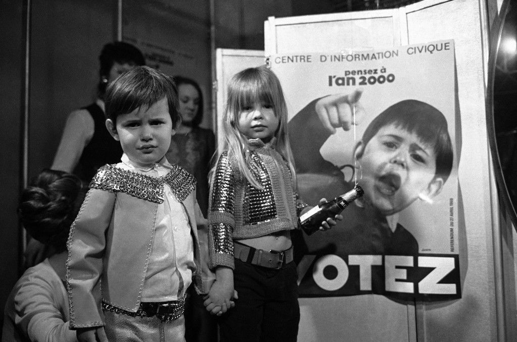 "Children model ""future"" clothing designed by Franco-Spanish couturier Paco Rabanne on March 29, 1969 in Paris, France. Poster for the year 2000 election in the background. (AP Photo/Michel Lipchitz)"