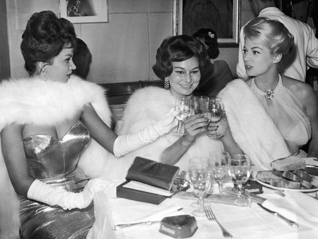 "Seated from left to right as they toast to a still better future are actresses: Chelo Alonso, Cuba; Caprice Chantal, France and Anita Ekberg, of Sweden. The toast was made in a Rome restaurant, Italy on Sept. 19, 1959, after the smiling young actresses, all of the movies, had received a ""Maschera d'Argento"" (Silver Mask) for their performances in the past year. The Silver Mask is kind of an Italian movie ""Oscar"" and is given once a year by the Rome journalists' association. The ""mask"" is also presented to outstanding personalities in the fields of radio/TV, music hall, prose and others. (AP Photo/Walter Attenni)"