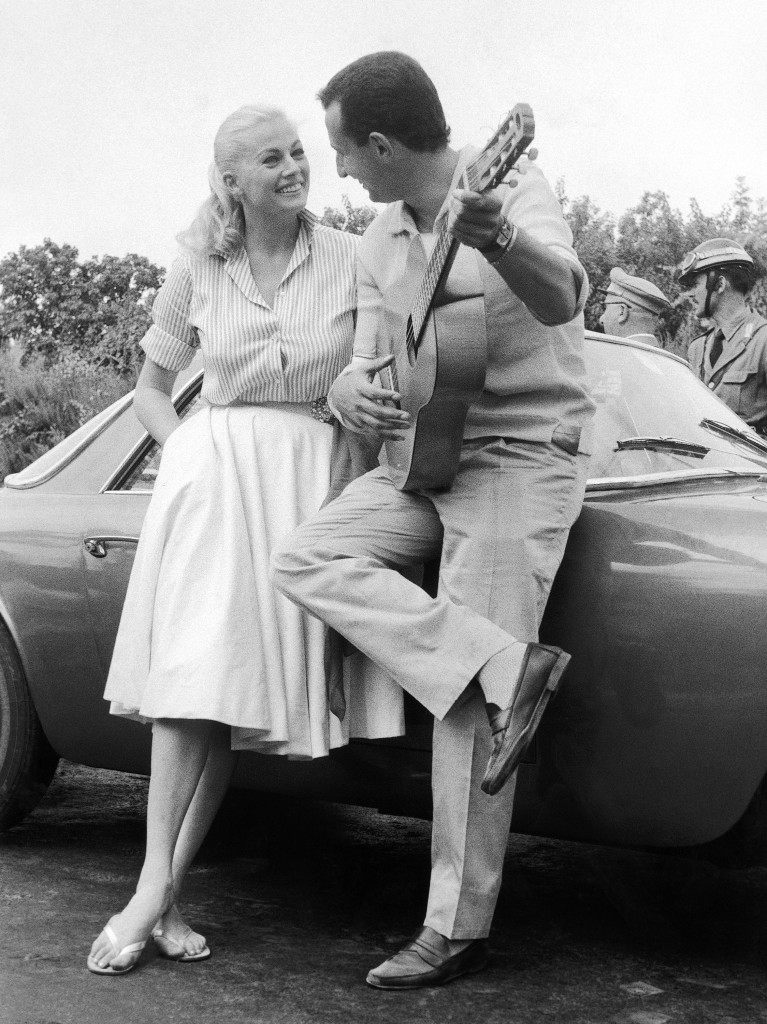 "Swedish-born movie star Anita Ekberg and her partner, Italian marchese Antonio Gerini, standing at their ""Lancia-Flaminia"" car during the first leg of the rally, the Rome-Salerno run on June 24, 1959 with which they are participating in the Italian Cinema Rally. This picture was taken during the first leg of the rally, the Rome-Salerno run on June 24, 1959. The Italian Cinema Rally also called ""The Stars' thousand miles Race"" runs from Rome, over Salerno, Catanzaro, Messina, Palermo, Catania and Mount Etna, to end at Taormina on the eastern coast of Sicily. It is divided into six legs. 23 cars have entered the race. They will be driven by Italian and foreign actresses, actors and other personalities of the movie, stage, radio and TV world, some of them accompanied by ""non-professional"" partners. (AP Photo/Dario Melchiorri)"