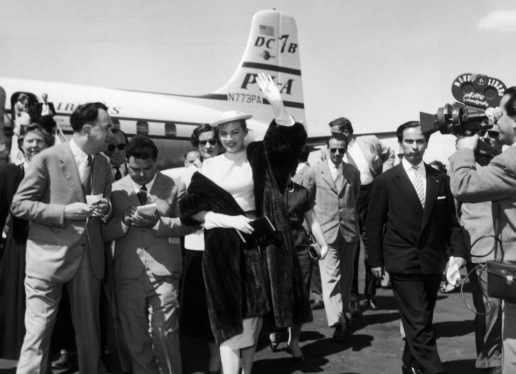 Swedish-born movie actress Anita Ekberg arrives at Rome''s Ciampino airport, Italy, from New York, and was met at the airport by her fiance, English film actor Anthony Steel (unseen). The couple will be married in a civil ceremony within a month in Florence where Steel is at work on a film. In this image Anita Ekberg surrounded by reporters, waves to a crowd of fans and photographers on May 11, 1956, as she walks away from the plane that brought her to Rome from New York. (AP Photo/Remo Nassi)