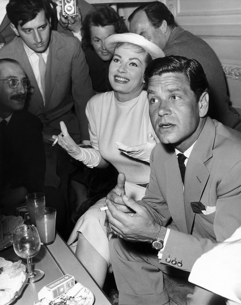 Swedish-born movie actress Anita Ekberg and her fiance, English film actor Anthony Steel smoke cigarettes while holding a press conference on May, 11, 1956 in a Rome hotel, Italy, and announced their plan to marry in a civil ceremony at Florence, where Steel is working on a film, between May 20 and 23, 1956. Miss Ekberg arrived earlier by plane from New York and was received at the Rome Ciampino airport by her future husband. (AP Photo/Walter Attenni)