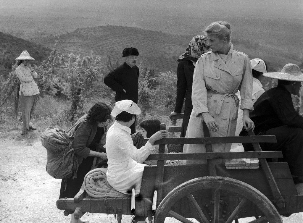 "Swedish-born actress Anita Ekberg stands in a Chinese cart, while refugees effort to load some of their belongings upon it, in a scene of a new Italian film, being shot in the woods near Tivoli, about 35 kilometers (22 miles) east of Rome, Italy on Sept. 26, 1959. The film is called ""Apocalisse sul Fiume Giallo"" (verbally: Apocalypse on the Yellow River). It tells the story of the nationalist Chinese forces' desperate fight against the communist forces, of the latter's plan to blow up a dike of the Yellow River, of an American journalist (played by French actor Georges Marchal) who happens to learn about this plan, and eventually saves the dike from a major disaster, and thus his love with an American nurse (played by Anita Ekberg). (AP Photo/Mario Torrisi)"