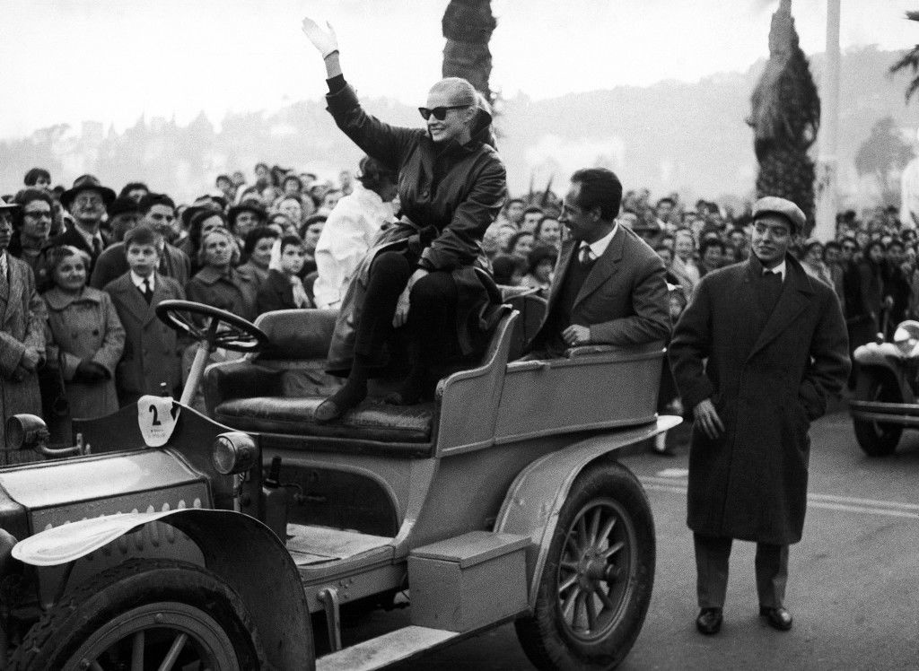 "Swedish-born actress Anita Ekberg, warmly dressed like the spectators on a cool day, waves from the top of a 1906 model automobile (Digion Bouton) with which she took part in a motorized carnival cortege in Rapallo, Italy on Feb. 8, 1959. Miss Ekberg, who is the wife of British actor Anthony Steel, is in Italy studying the script of her part in star director Federico Fellini (La Strada) new movie ""La Dolce Vita"" (The Sweet Life). (AP Photo/Gino Calza)"
