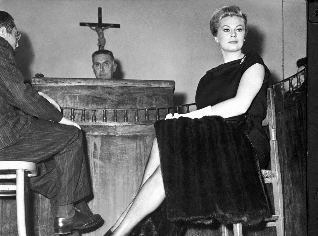 "Swedish-born movie actress Anita Ekberg sits in a court room at Castrovillari, near Cosenza, southern Italy, on May 5, 1960, as she was questioned about injuries to ten persons, allegedly caused by a car in which she was participating in an ""automobile rally of stars"" in June 1959. In background sits the judge, Antonio Lupone. Miss Ekberg was riding in a car driven by Italian marchese Antonio Gerini, in a parade heading from Rome to Sicily. At Castrovillari a big group of fans gathered round the car during a rally halt. Police said the Marchese started to drive away while the fans were still around the car, injuring ten. Newspapers reported at the time that the fans were particularly attracted because a button was missing from Anita's blouse at a most strategic point, but she denied that in court. The next hearing in the case will be May 12, 1960. (AP Photo)"