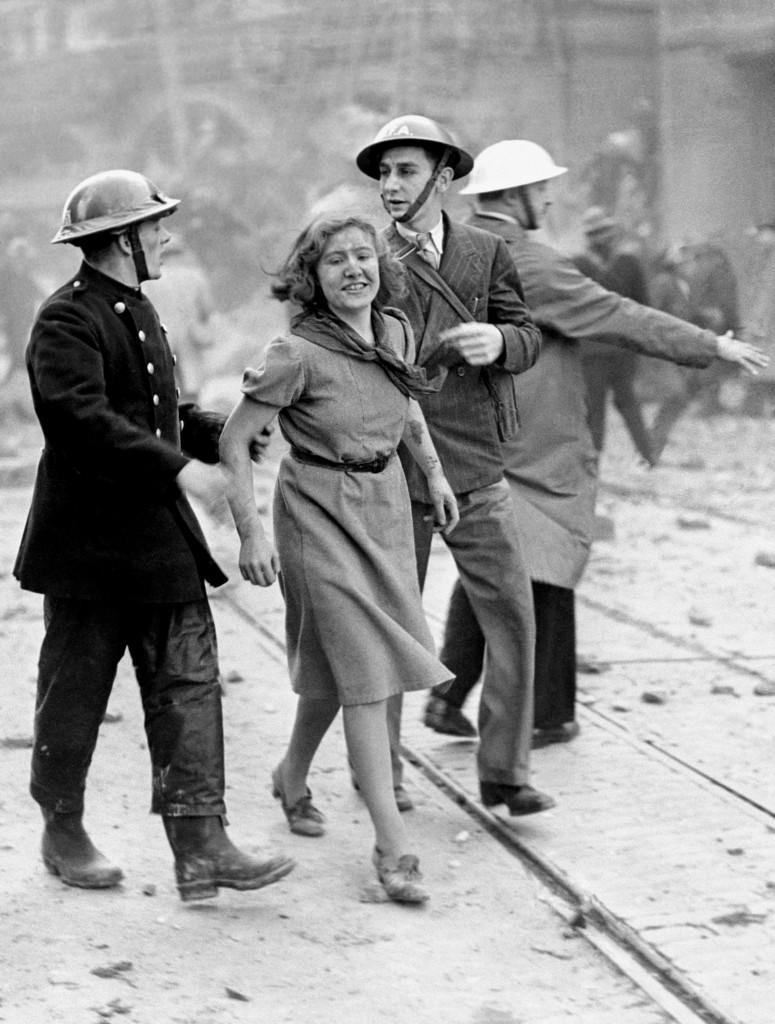 A city girl worker still smiling after being rescued from a London building just wrecked by a bomb dropped by a daylight German Luftwaffe raid.