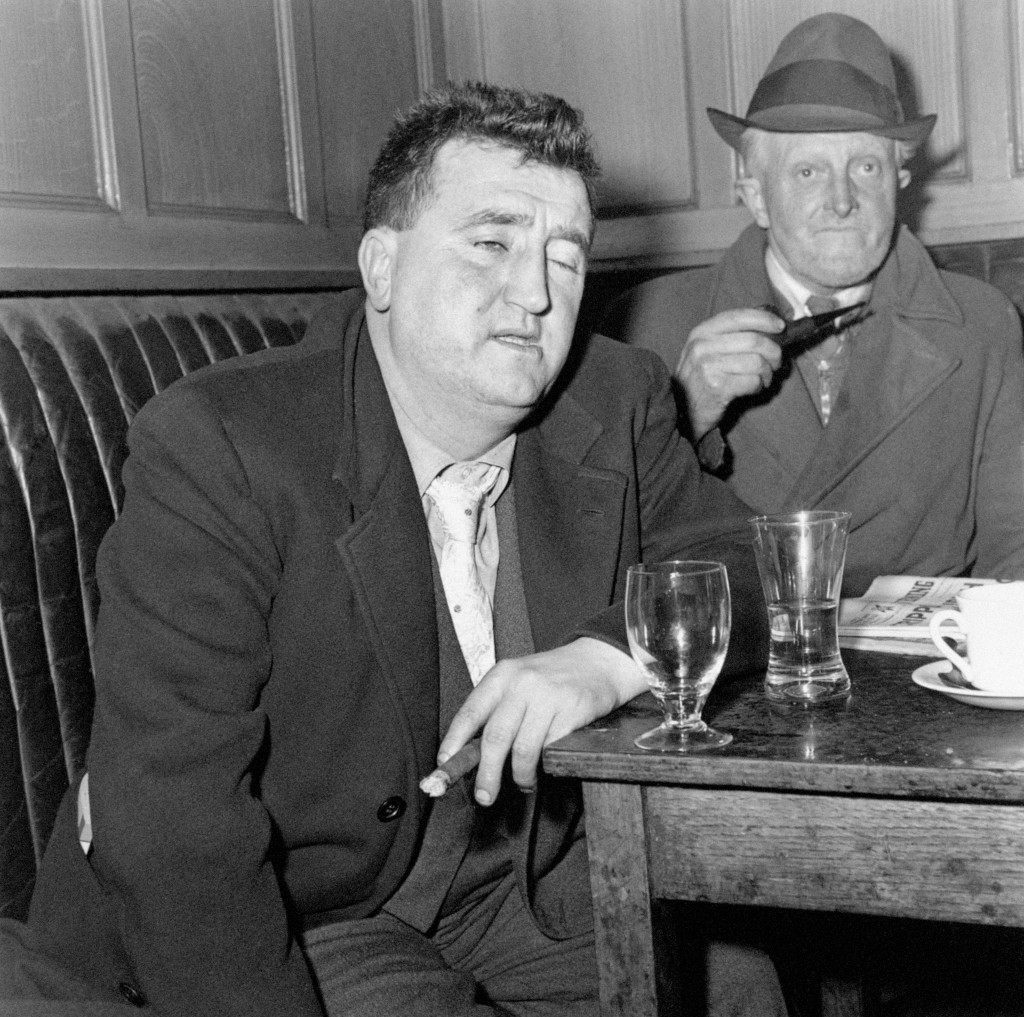 "Irish playwright Brendan Behan, whose plays ""The Quare Fellow"" and ""The Hostage"" were enthusiastically received in London's West End, enjoys a drink and a chat with his friend Michael Collins in Tom Moore's Bar in Dublin, Ireland. Picture date:February 9, 1961. Ref #: PA.2414430"