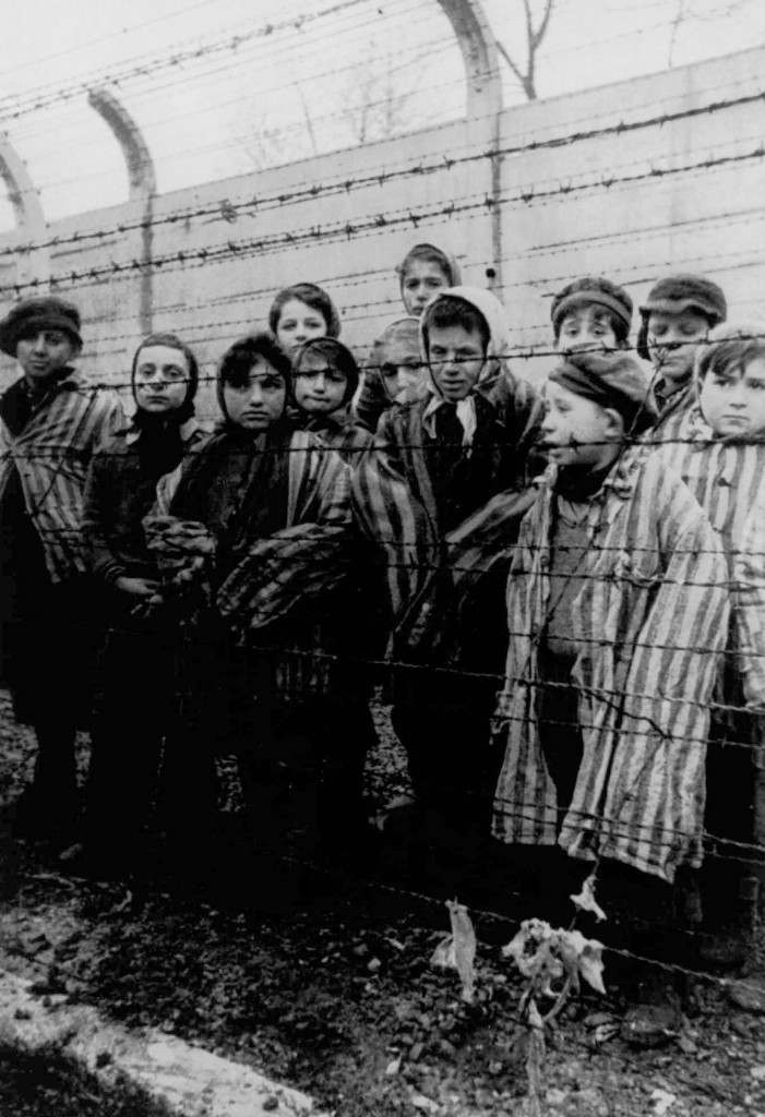 Pasa Balter, fourth from left, stands among a group of children wearing concentration camp uniforms behind barbed wire fencing as they were liberated from the Nazi concentration camp at Auschwitz, Poland by Russian soldiers in April, 1945. Balter, who is now known as Paula Lebovics, is 61 and living in Encino, Calif., a survivor who bears the heartbreak of having lost most of her family. (AP Photo/ho) Ref #: PA.4763052