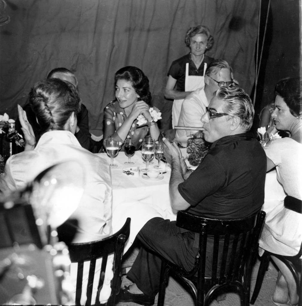 Aristotle Onassis, foreground with cigar, and Italian opera singer Maria Callas, center background, are shown at a restaurant party in Portofino, Italy, on July 10, 1961. They are cruising the Mediterranean on Onassis' yacht Christina, which is anchored off Portofino. (AP Photo)